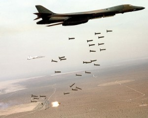 A B1 bomber dropping hundred of undirected 'dumb' bombs that indiscriminately destroy. maim and kill civilians.